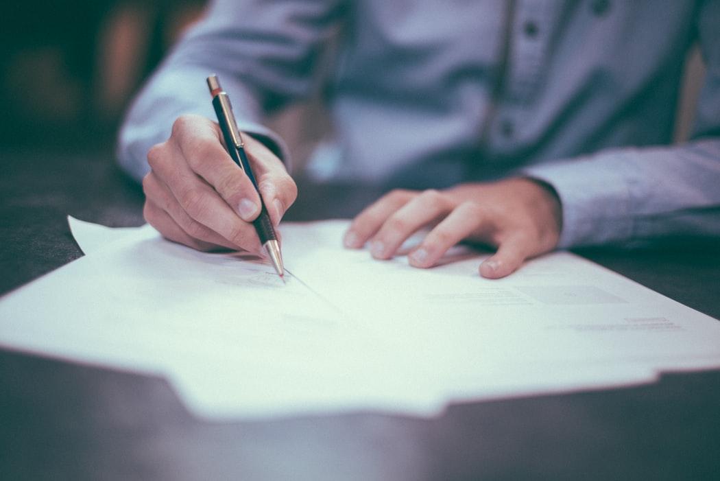 image of man signing paper
